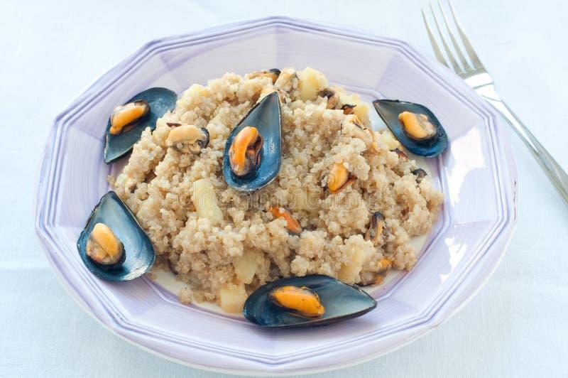 Ensalada caliente de la quinoa con los mejillones, los tomates y las patatas imagen de archivo libre de regalías