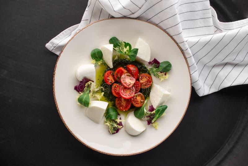 Ensalada caprese italiana con los tomates cortados, queso de la mozzarella, albahaca, aceite de oliva en fondo negro fotografía de archivo