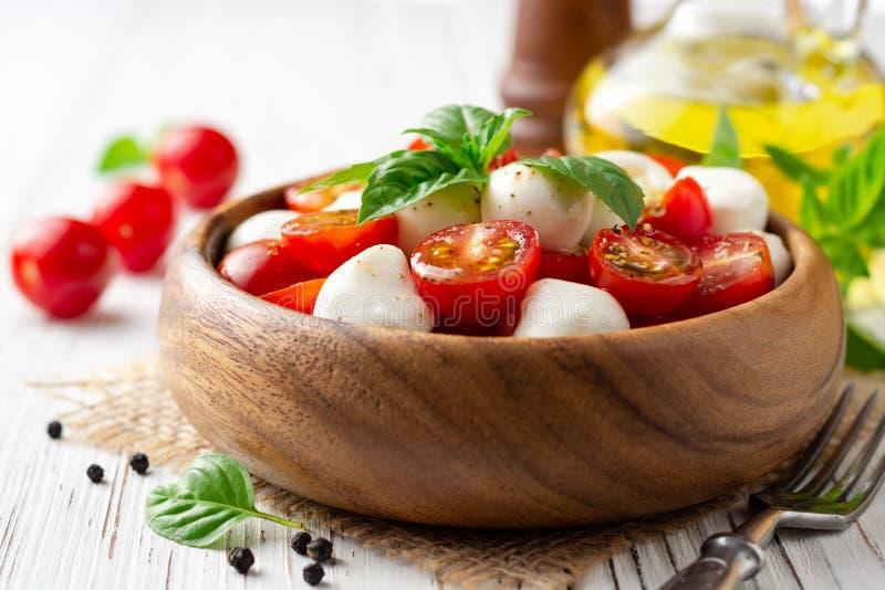 Ensalada caprese italiana con los tomates de cereza, el queso de la mozzarella y la albahaca en el fondo de madera blanco foto de archivo