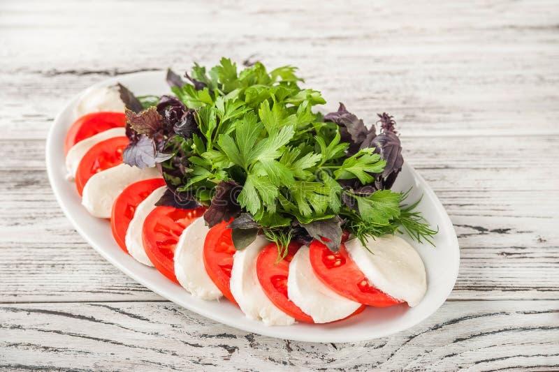 Ensalada caprese italiana fácil en un primer blanco de la placa Mozzarella, tomates, albahaca, salsa en el espacio de la copia de imagen de archivo libre de regalías