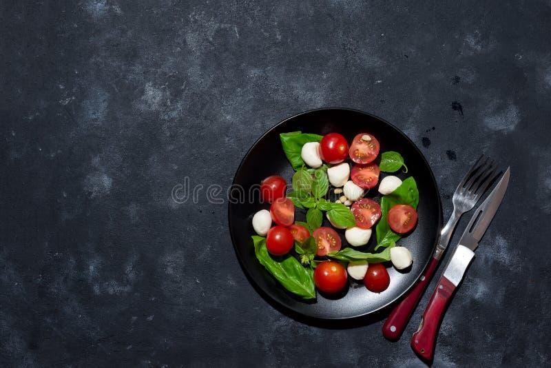Ensalada caprese italiana fresca con la mozzarella y los tomates en la placa negra sobre fondo de piedra oscuro con el espacio de imagenes de archivo