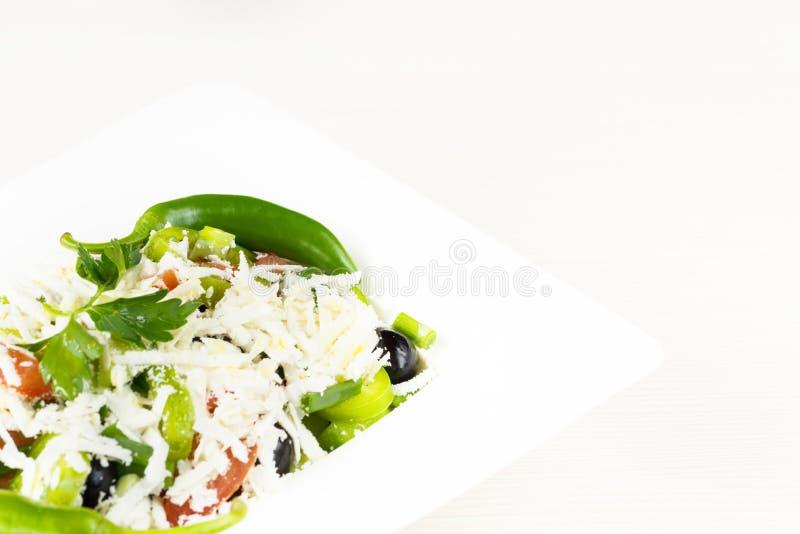 Ensalada clásica tradicional de Shopska con los tomates, las pimientas, los pepinos y el queso en el plato blanco en la tabla de  imágenes de archivo libres de regalías