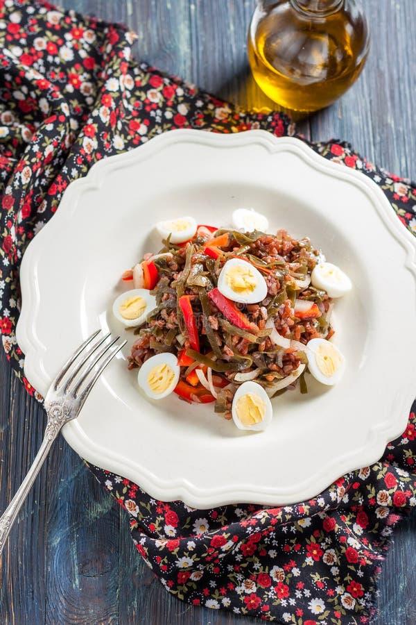 Ensalada con alga marina, los huevos, el arroz y la pimienta roja imagen de archivo