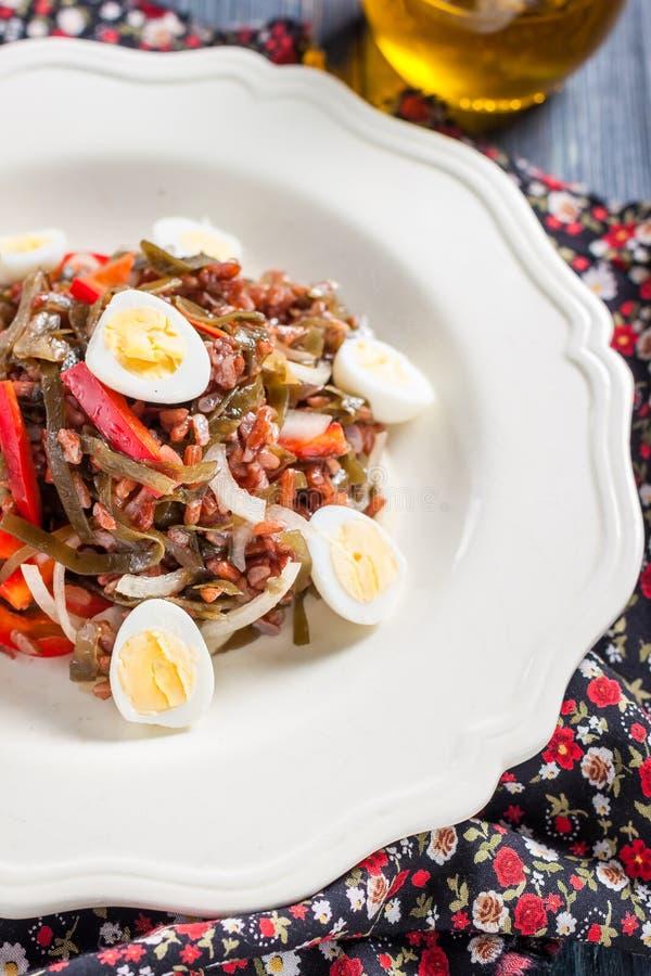 Ensalada con alga marina, los huevos, el arroz y la pimienta roja fotografía de archivo