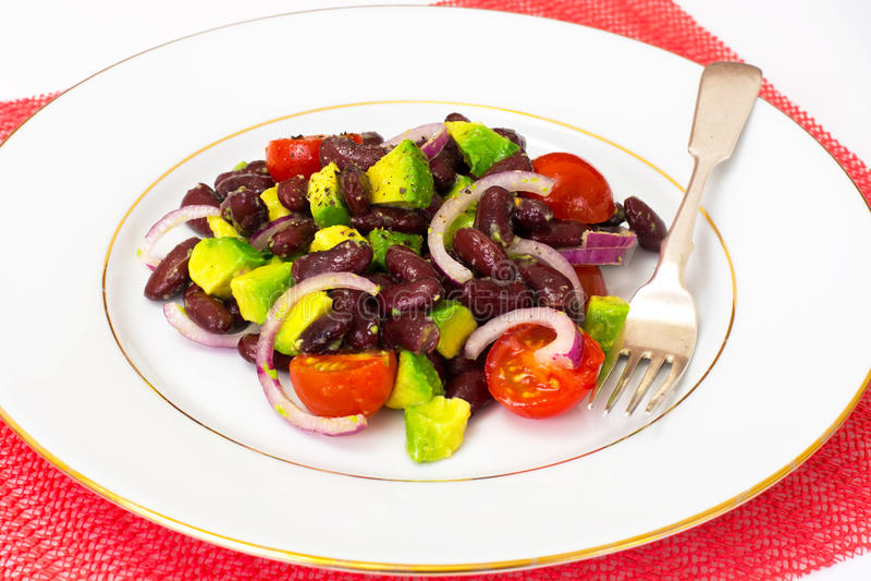 Ensalada con el aguacate, las habas, los tomates de cereza, la cebolla roja y el vegeta imagen de archivo