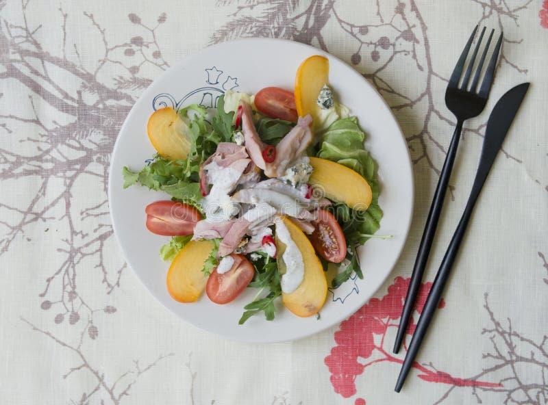Ensalada con el caqui, el pollo ahumado, los tomates de cereza, el queso del camembert y la salsa del queso verde Plato festivo C fotos de archivo