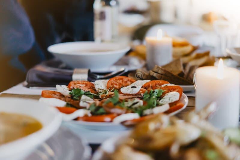Ensalada con el desayuno del tomate, del mozzarela, de la basílica en el tablero de madera en la tabla de cocina, del concepto de fotografía de archivo libre de regalías