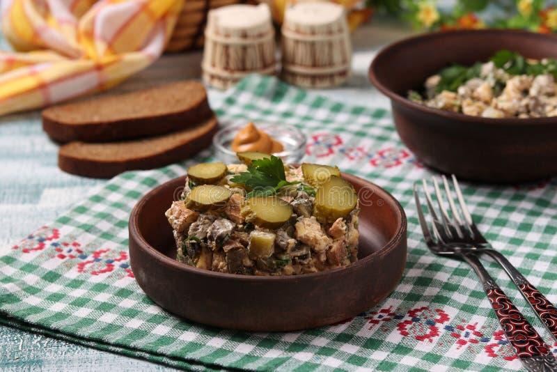 Ensalada con el hígado de pollo, la tortilla y los pepinos conservados en vinagre fotografía de archivo
