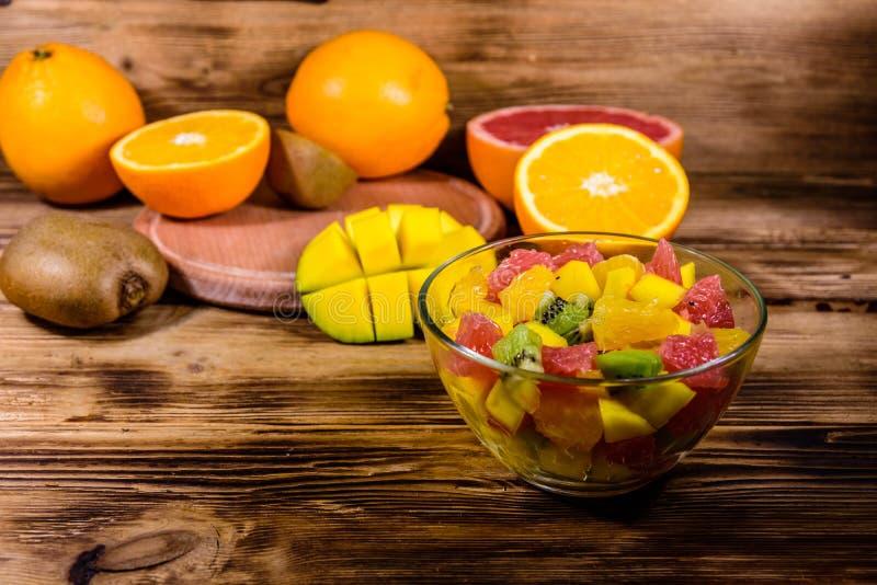Ensalada con el mango, las naranjas, el pomelo y los kiwis en un bol de vidrio en la tabla de madera fotografía de archivo