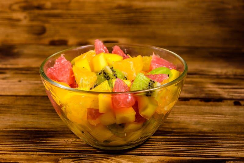 Ensalada con el mango, las naranjas, el pomelo y los kiwis en un bol de vidrio en la tabla de madera imagenes de archivo