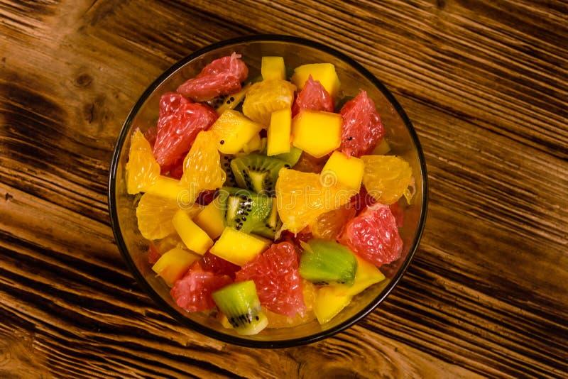 Ensalada con el mango, las naranjas, el pomelo y los kiwis en un bol de vidrio en la tabla de madera Visi?n superior fotografía de archivo
