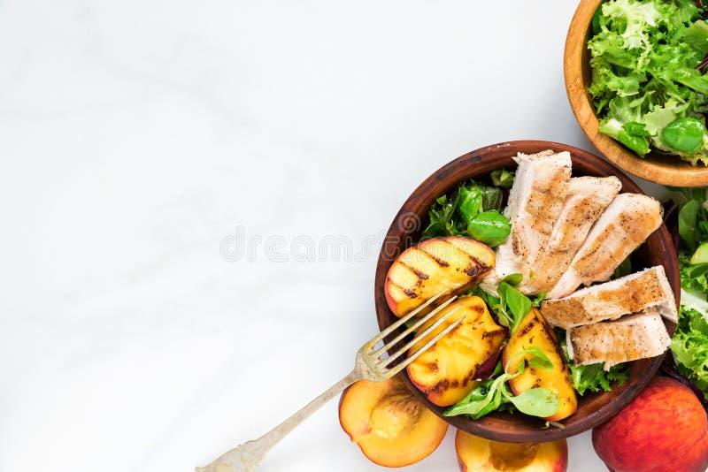 Ensalada con el pollo asado a la parrilla y melocotón en un cuenco con la bifurcación Alimento sano Visión superior imagenes de archivo