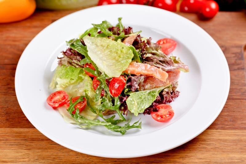 Ensalada con el salmón ahumado, los tomates, la lechuga y el arugula en la placa blanca imagen de archivo
