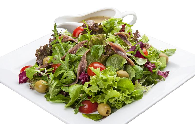 Ensalada con las anchoas y las verduras en una placa blanca fotos de archivo libres de regalías