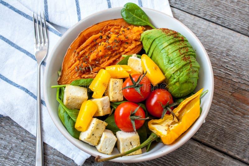 Ensalada con las verduras asadas a la parrilla: patatas dulces asadas a la parrilla, tomates, aguacates, espinaca, queso de soja, foto de archivo libre de regalías