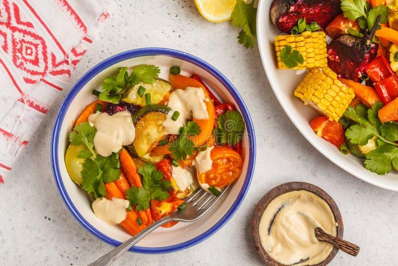 Ensalada con las verduras cocidas con tahini en la placa blanca, vagos blancos fotos de archivo libres de regalías