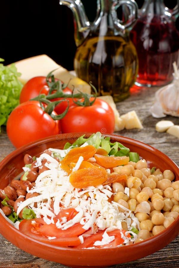 Ensalada con los garbanzos, tomate, queso foto de archivo
