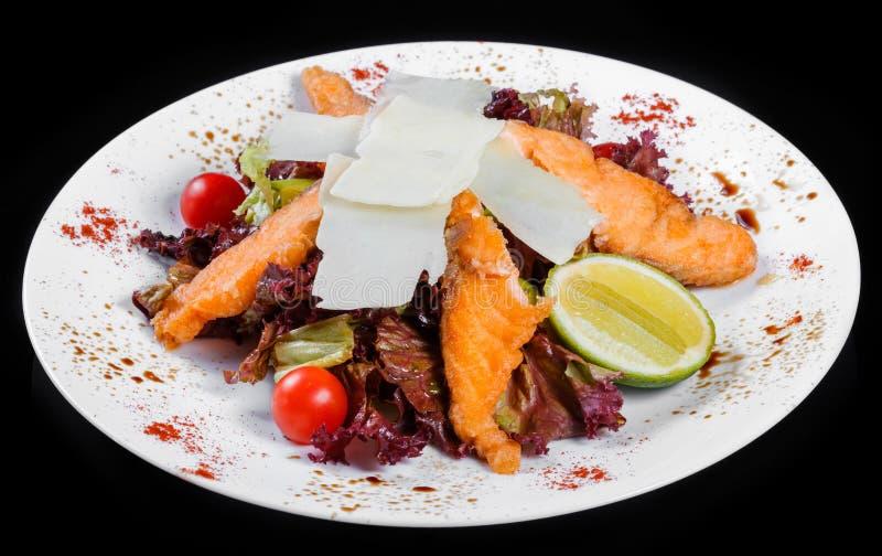Ensalada con los salmones asados a la parrilla, queso parmesano, tomates, verdes mezclados, lechuga y cal, aisladas fotografía de archivo