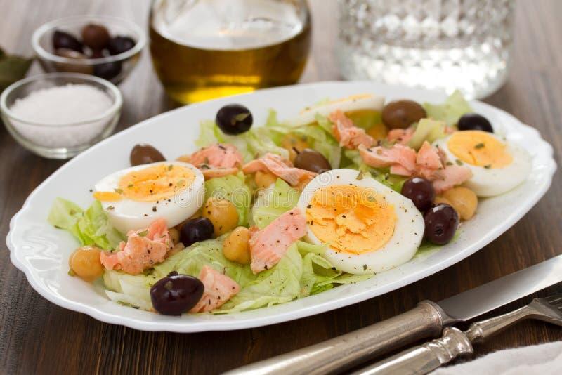 Ensalada con los salmones, los huevos y las aceitunas en el plato blanco imagenes de archivo