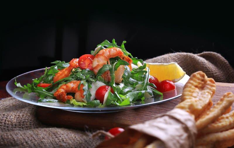 Ensalada con los tomates del arugula y de cereza con el camarón, rebanadas de limón y parmesano imagen de archivo