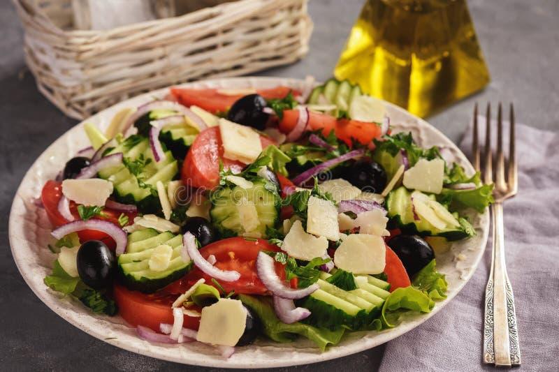 Ensalada con los tomates, los pepinos, las aceitunas, la cebolla roja y el queso parmesano imagen de archivo