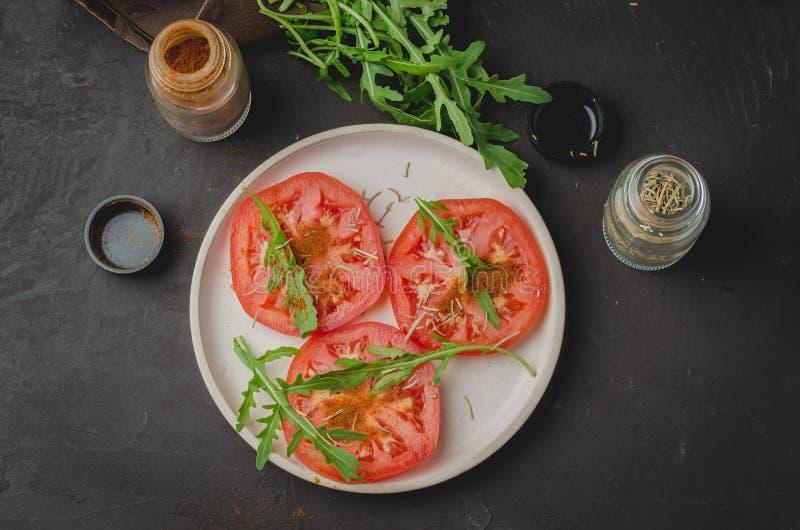 Ensalada cortada de los tomates y de las especias del arugula Alimento sano Visi?n superior imagenes de archivo