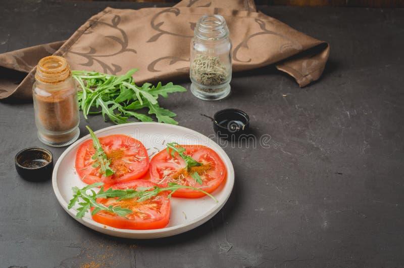 ensalada cortada de los tomates y de las especias del arugula Comida sana en un fondo oscuro Copie el espacio fotografía de archivo