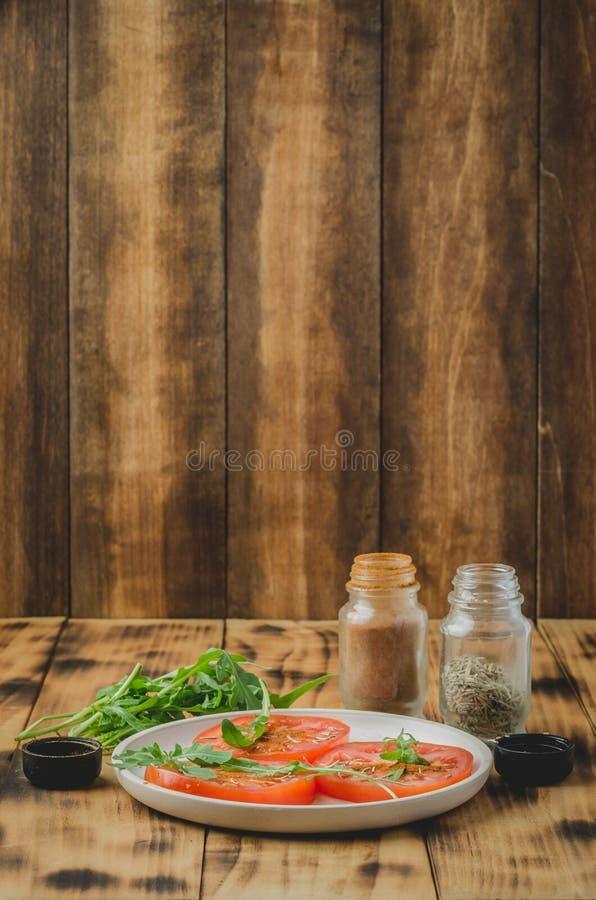 Ensalada cortada de los tomates y de las especias del arugula En un cuenco blanco en un fondo de madera Foco selectivo imagenes de archivo