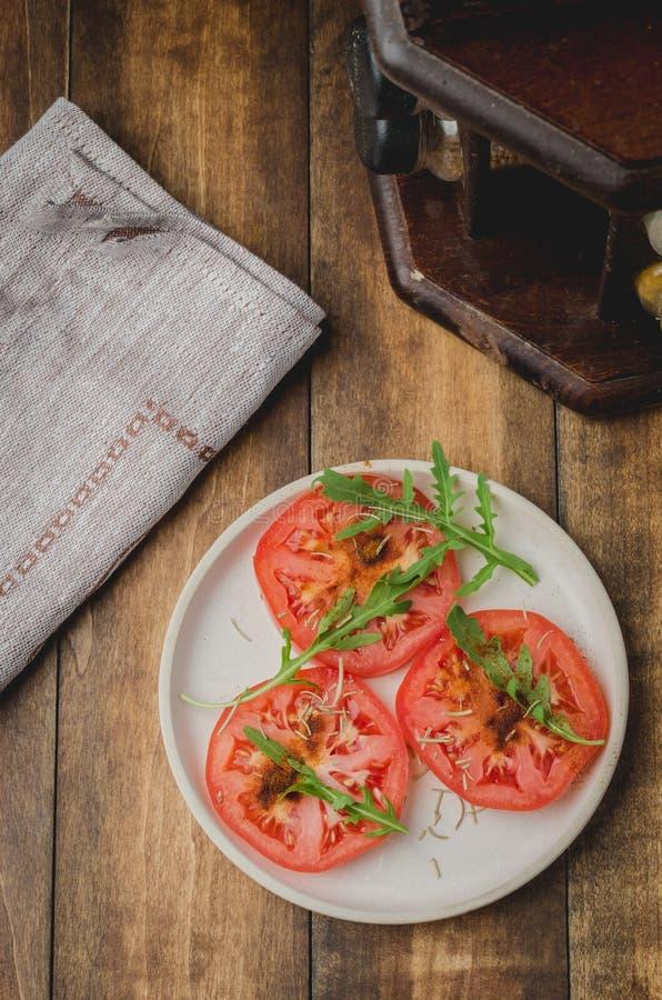 Ensalada cortada de los tomates y de las especias del arugula En un cuenco blanco en un fondo de madera Visi?n superior fotografía de archivo libre de regalías