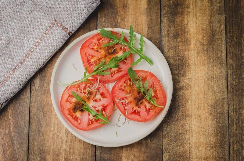 Ensalada cortada de los tomates y de las especias del arugula En un cuenco blanco en un fondo de madera Visi?n superior foto de archivo libre de regalías