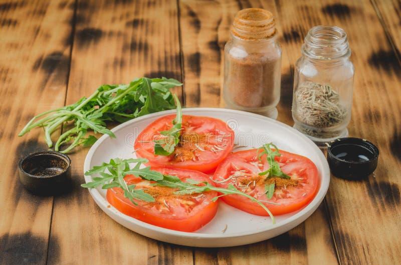 Ensalada cortada de los tomates y de las especias del arugula En un cuenco blanco en una tabla de madera Foco selectivo foto de archivo