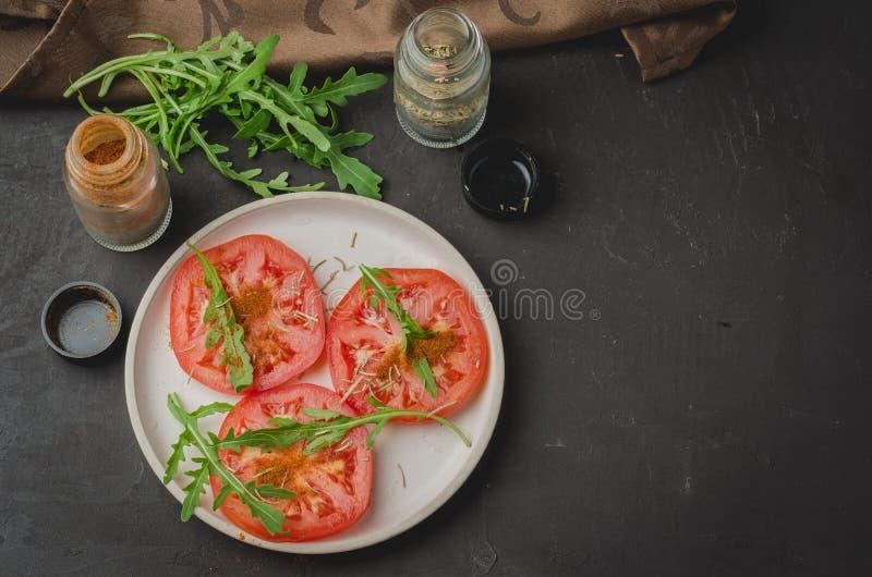 Ensalada cortada de los tomates y de las especias del arugula Ensalada sana de la comida en un fondo oscuro Copie el espacio y la fotos de archivo