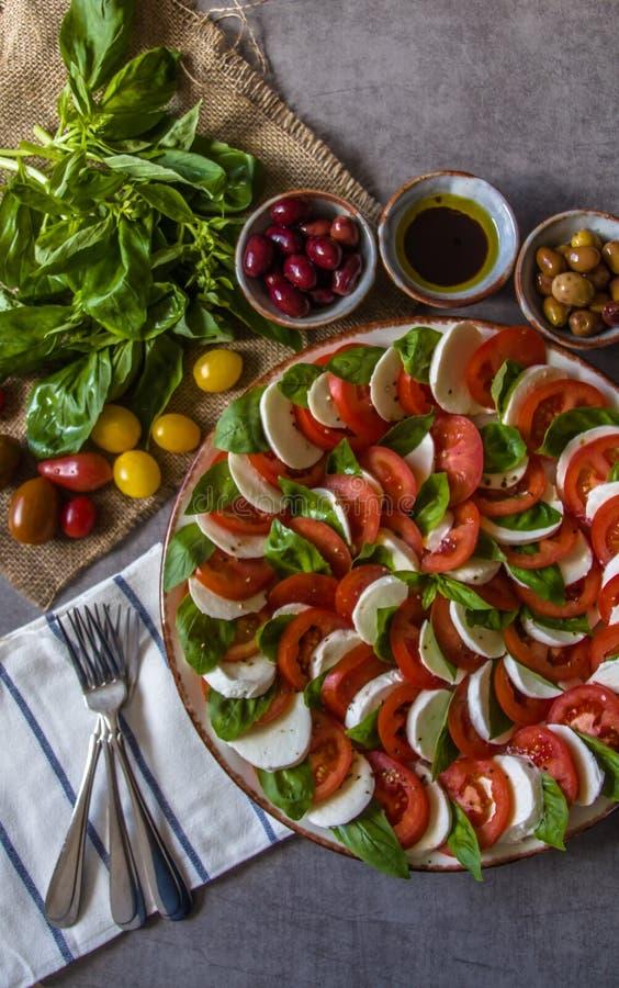 Ensalada de Caprese - hizo de la mozzarella fresca cortada, tomates, hojas de la albahaca dulce, con las aceitunas, las bifurcaci imagen de archivo
