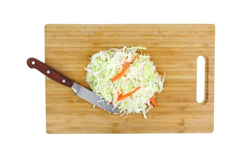 Ensalada de col en tabla de cortar con el fondo del blanco del cuchillo foto de archivo