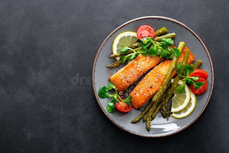 Ensalada de color salmón asada a la parrilla del filete de pescados, del espárrago, del tomate y de maíz en la placa Plato sano p foto de archivo libre de regalías