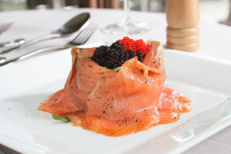 Ensalada de color salmón con el cohete y el caviar imagenes de archivo