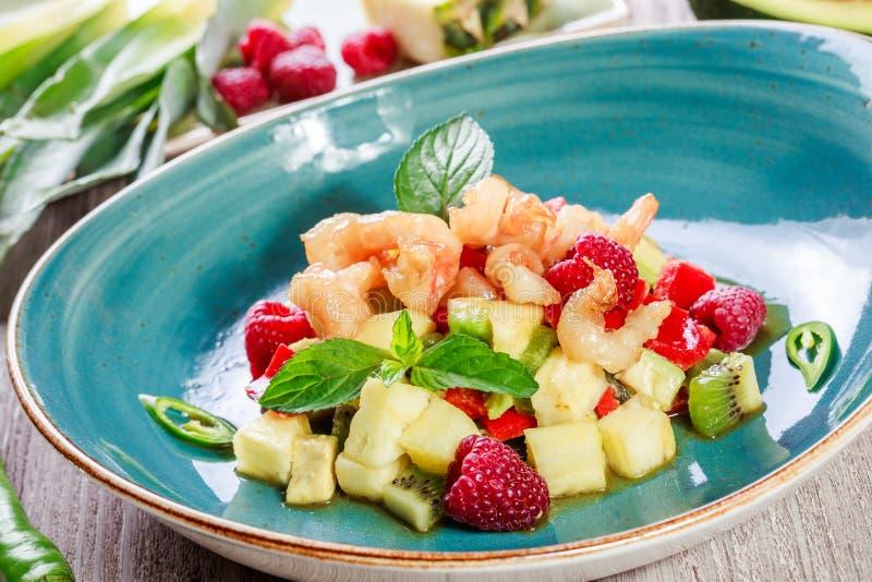 Ensalada de fruta con el camarón, aguacate, pimienta búlgara, kiwi, piña, frambuesas en placa en cierre de madera del fondo para  imagen de archivo