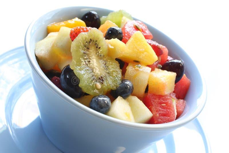 Ensalada de fruta en tazón de fuente azul fotografía de archivo libre de regalías
