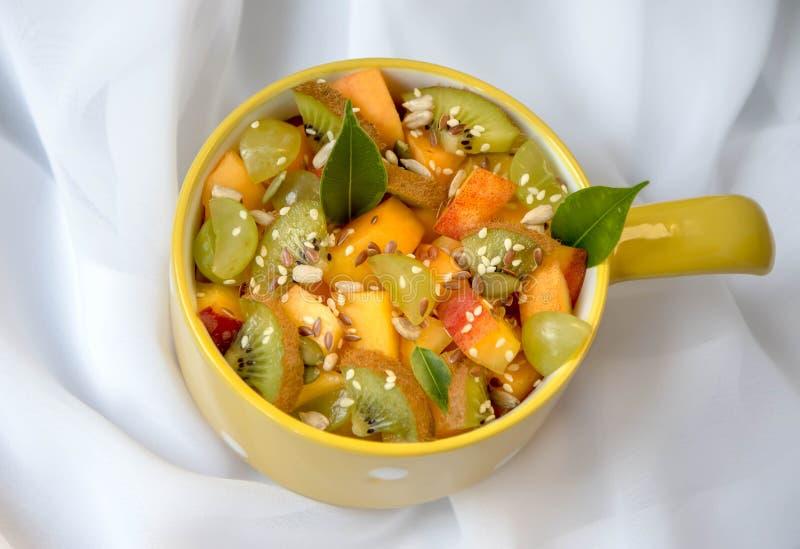 Ensalada de fruta, en un fondo blanco, con las hojas verdes fotos de archivo libres de regalías