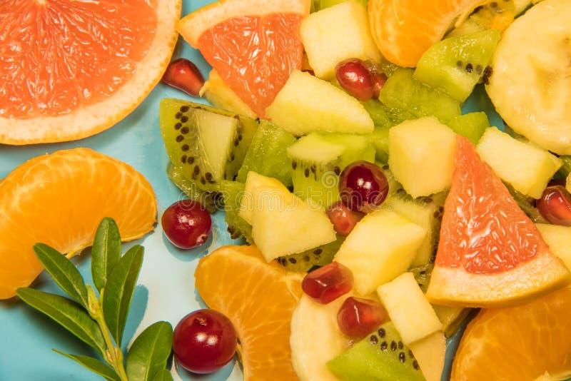 Ensalada de fruta fresca con la fruta cítrica en un fondo azul con un lugar para la inscripción Ensalada fresca de la fruta cítri imagenes de archivo