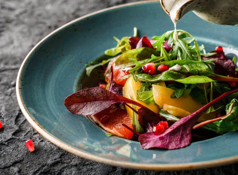 Ensalada de fruta fresca sana con verdes y salsa en cuenco sobre fondo oscuro Comida sana, vegetariano que adieta, cierre para ar foto de archivo libre de regalías