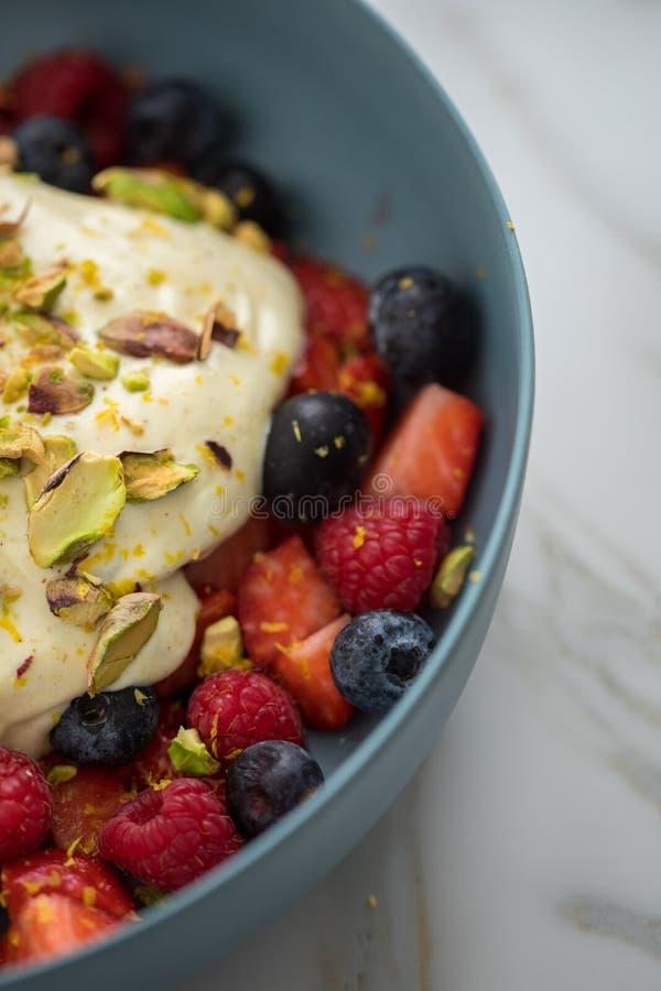 Ensalada de la baya con las fresas, los arándanos, la frambuesa, el pistacho, el ánimo de limón y la crema del quark del aceite d imagen de archivo