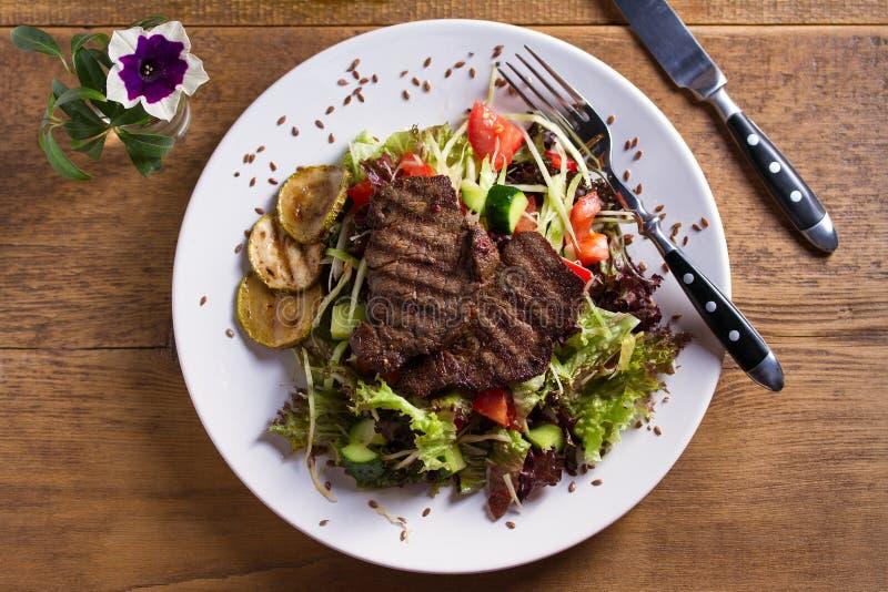 Ensalada de la carne de vaca: filetes de carne de vaca asados a la parrilla con los tomates, pepinos, calabacín, lechuga y col, a fotografía de archivo