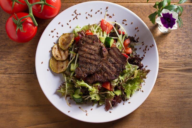 Ensalada de la carne de vaca: filetes de carne de vaca asados a la parrilla con los tomates, pepinos, calabacín, lechuga y col, a fotos de archivo
