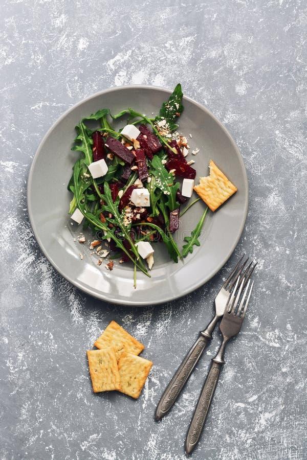 Ensalada de la dieta del vegano con las remolachas, arugula, queso feta con las galletas, fondo gris El concepto de consumición s imagenes de archivo