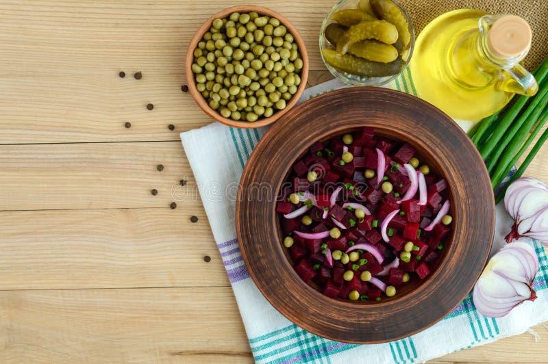 Ensalada de la vitamina de las remolachas, guisantes verdes, cebolla azul en un cuenco de la arcilla Ingredientes para cocinar foto de archivo libre de regalías
