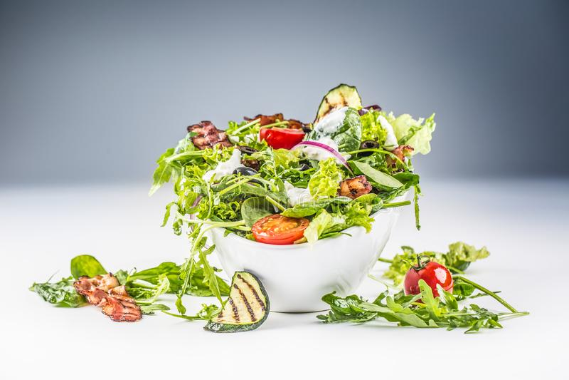Ensalada de las verduras frescas con la preparación del tzatziki del calabacín del arugula de las aceitunas de los tomates del to imagen de archivo