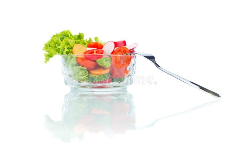 Ensalada de las verduras frescas en bol de vidrio con la bifurcación aislada en blanco imagen de archivo