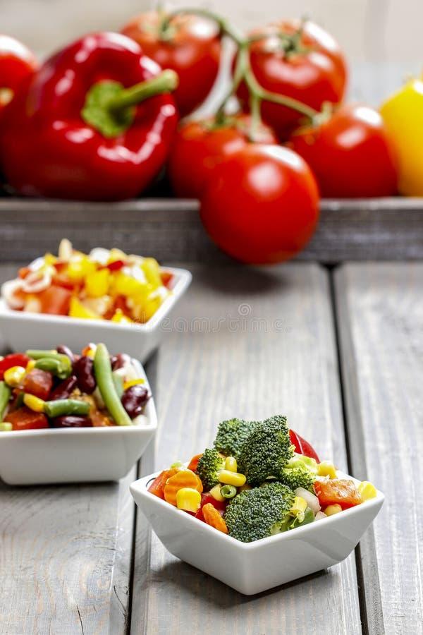 Ensalada de las verduras frescas en el cuenco blanco Tabla del partido de la primavera imagenes de archivo