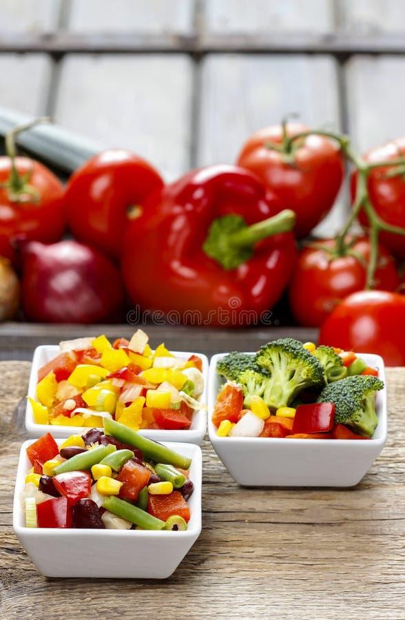 Ensalada de las verduras frescas en el cuenco blanco Tabla del partido de la primavera fotografía de archivo libre de regalías